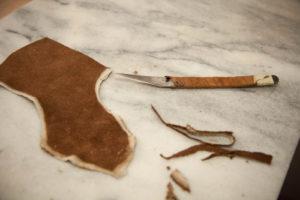 Das Leder für Maßschuhe wird mit einem scharfen Messer zugeschnitten